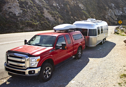 Auto Plus Insurance Group LLC   Red truck parked on the side of a road near a mountain with a silver RV attached to the back and a luggage rack on top