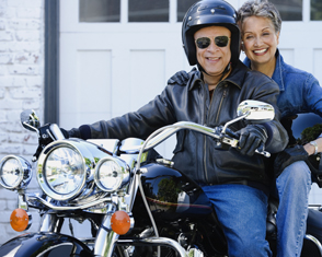 Auto Plus Insurance Group LLC | Retired couple on back of a motorcycle parked in front of their home's garage
